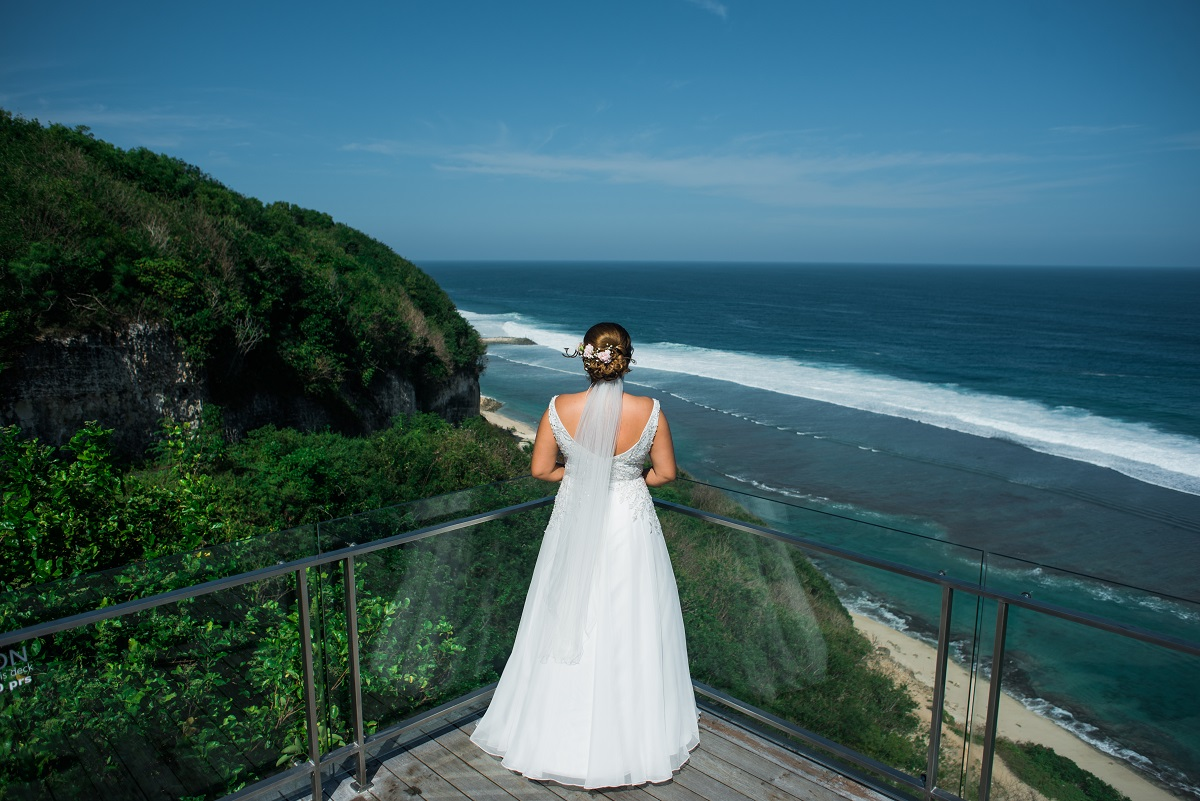 Braut schaut auf den Ozean in Bali