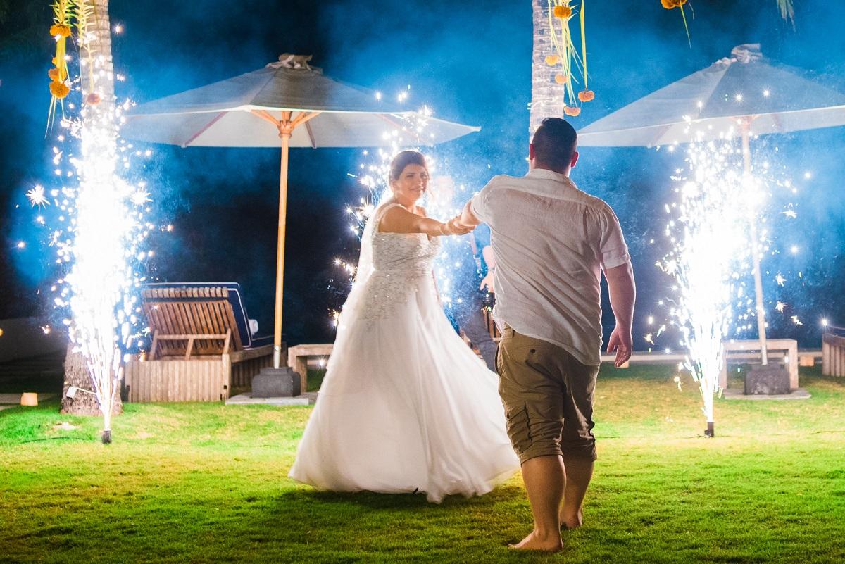 Brautpaar tanzt ausgelassen mit Feuerwerk
